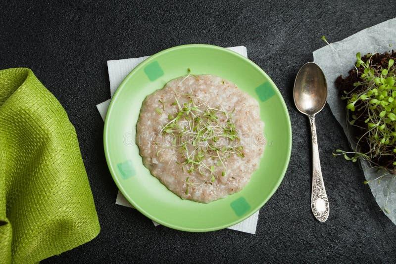 Morgonfrukost, organisk havremjöl med mikrogräsplaner på en svart bakgrund En handduk, en tappningsked och unga salladgroddar arkivbilder