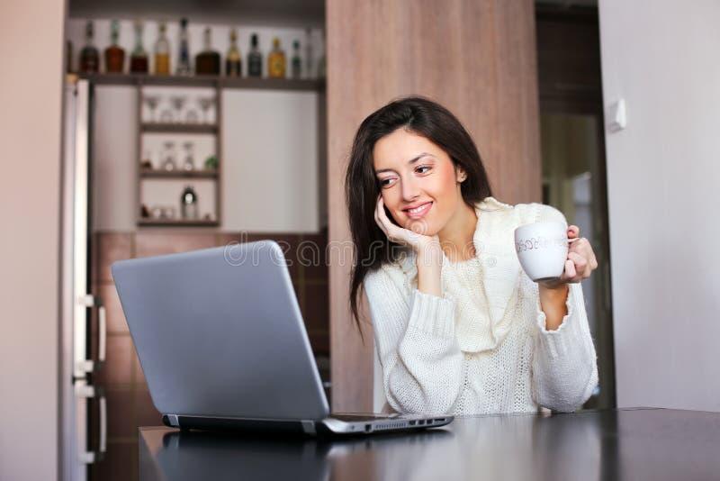 Morgonkaffe framme av en bärbar dator royaltyfria bilder