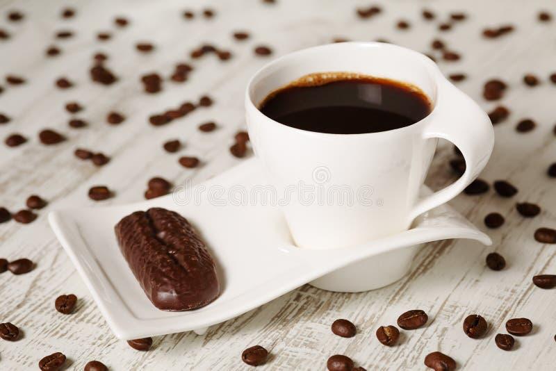Morgonkaffe i den vita keramiska koppen med vågen formade tefat- och chokladkexet på den vita trälantliga tabellen med spridd cof royaltyfri foto