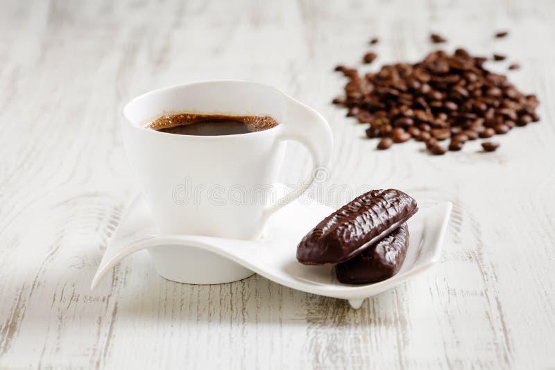 Morgonkaffe i den vita keramiska koppen med vågen formade tefatet, och två kakaokex i kaffeböna formar på den vita trälantliga fl royaltyfri foto