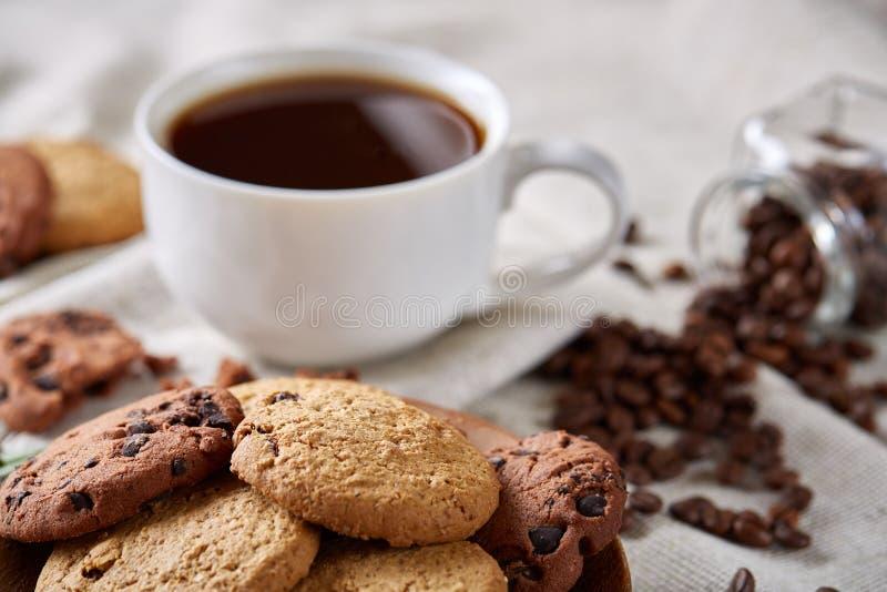 Morgonkaffe i den vita koppen, kakor för chokladchiper på skärbrädanärbilden, selektiv fokus arkivbild