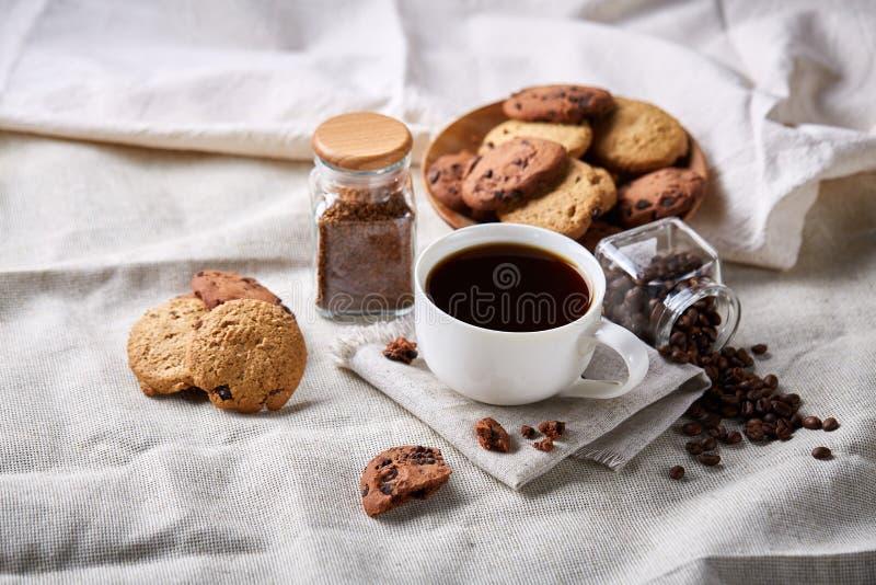 Morgonkaffe i den vita koppen, kakor för chokladchiper på skärbrädanärbilden, selektiv fokus arkivfoto