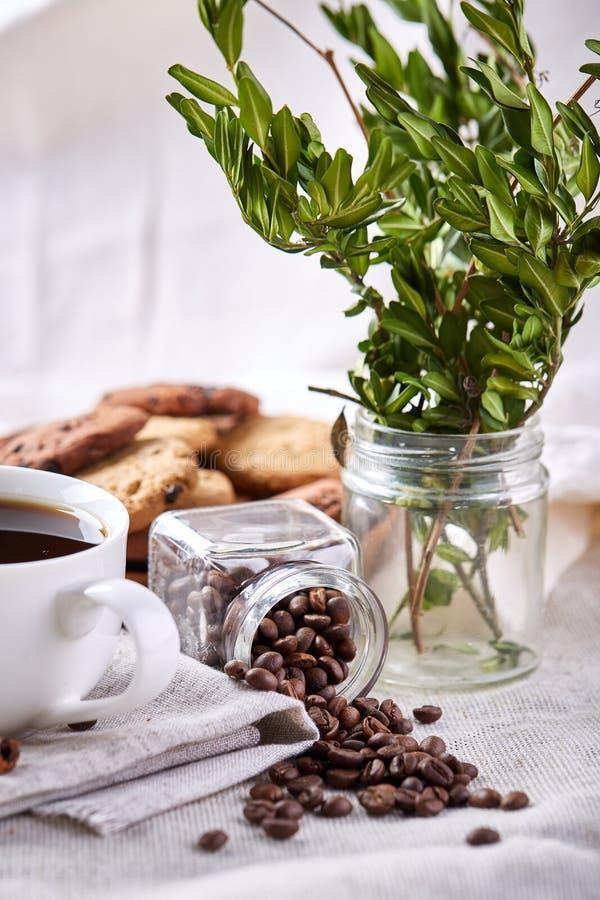 Morgonkaffe i den vita koppen, kakor för chokladchiper på skärbrädanärbilden, selektiv fokus royaltyfria bilder