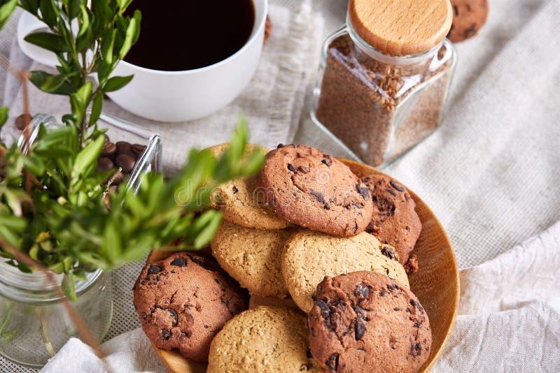 Morgonkaffe i den vita koppen, kakor för chokladchiper på skärbrädanärbilden, selektiv fokus royaltyfri foto