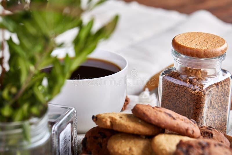 Morgonkaffe i den vita koppen, kakor för chokladchiper på skärbrädanärbilden, selektiv fokus royaltyfria foton