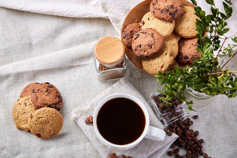 Morgonkaffe i den vita koppen, kakor för chokladchiper på skärbrädanärbilden, selektiv fokus royaltyfri fotografi