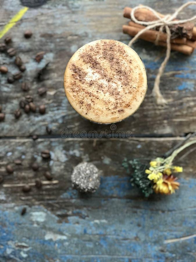 Morgonkaffe i den vita koppen med dekorativ torkad blomma-, sked-, kanel- och kaffebönabakgrund på tabellöverkant, värme signal,  royaltyfria bilder