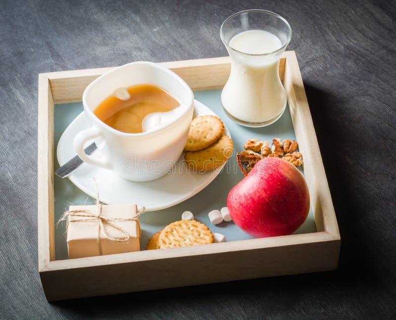 Morgonkaffe med marshmallower, kakor och mjölkar i träask mörkt trä för bakgrund arkivbild