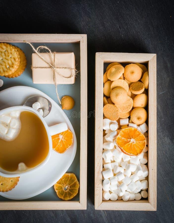 Morgonkaffe med marshmallower, kakor och mjölkar i träask mörkt trä för bakgrund royaltyfri fotografi