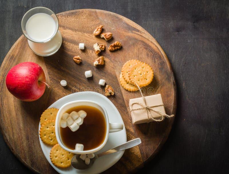 Morgonkaffe med marshmallower, kakor och mjölkar mörkt trä för bakgrund arkivfoto
