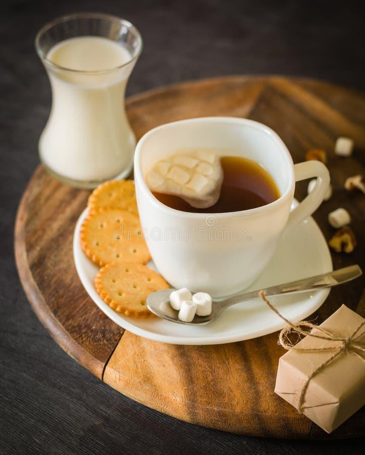 Morgonkaffe med marshmallower, kakor och mjölkar mörkt trä för bakgrund arkivfoton