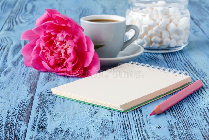 Morgonkaffe rånar, tom anteckningsbok-, blyertspenna- och vitpionflowe arkivbilder