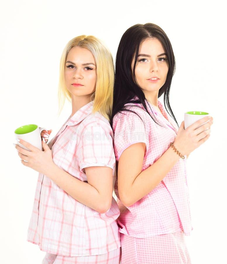 Morgonkaffebegrepp Blondinen och brunetten på sömniga framsidahåll rånar med kaffe Systrar eller bästa vän i pyjamas royaltyfri bild