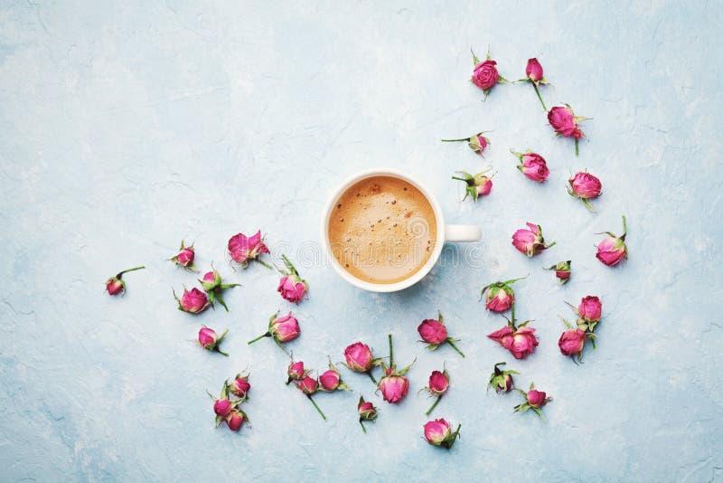 Morgonkaffekoppen och torkar rosa blommor på blå bästa sikt för tappningtabell i lekmanna- stil för lägenhet Hemtrevlig frukost p royaltyfri bild