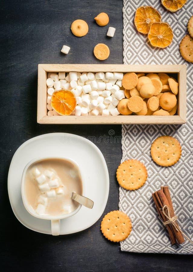Morgonkakao med marshmallower, kakor och mjölkar i träask mörkt trä för bakgrund royaltyfria bilder