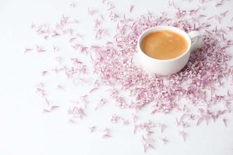 Morgonkopp kaffe och lila blommor på ljus bakgrund, bästa sikt Lekmanna- stil f?r hemtrevlig frukostl?genhet Kvinnlig kvinnadag m royaltyfria foton