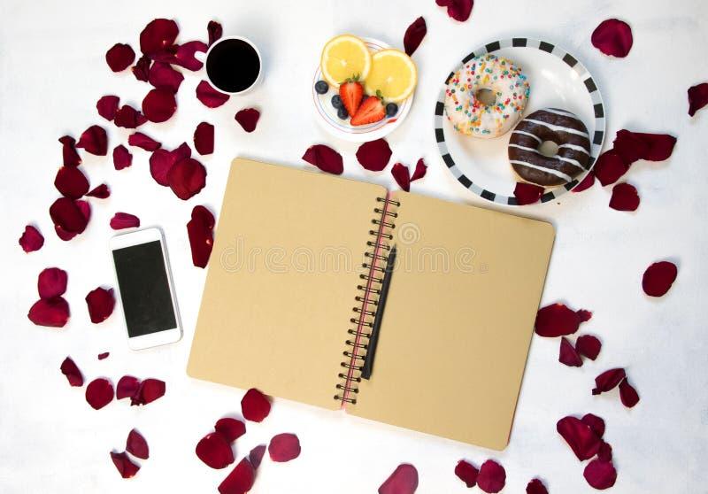 Morgonkopp kaffe, tomma anteckningsbok- och rosblommor, frukter och donuts på den vita tabellen från över Hemtrevlig frukost royaltyfri bild