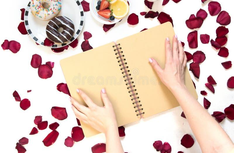 Morgonkopp kaffe, tomma anteckningsbok- och rosblommor, frukter och donuts på den vita tabellen från över Hemtrevlig frukost arkivfoton