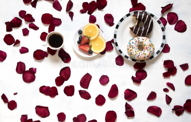 Morgonkopp kaffe, tomma anteckningsbok- och rosblommor, frukter och donuts på den vita tabellen från över Hemtrevlig frukost royaltyfria bilder