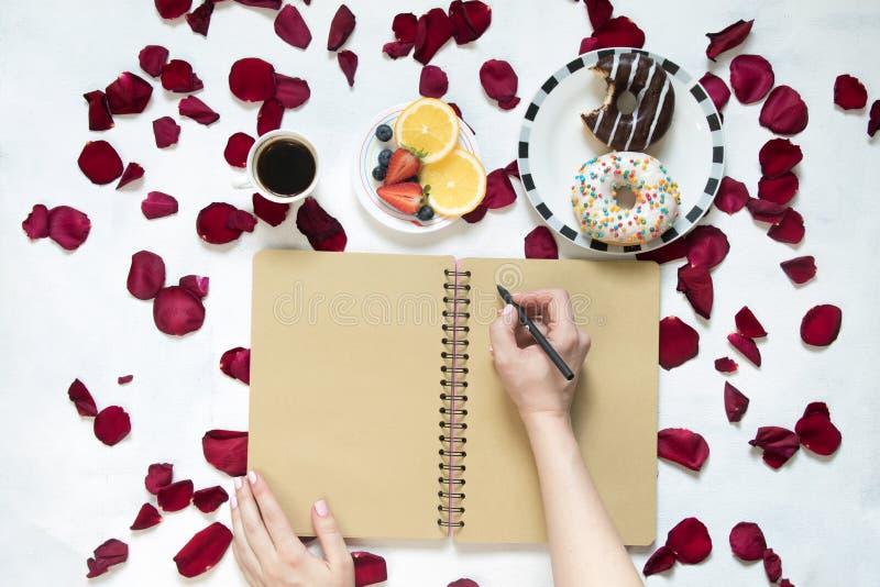 Morgonkopp kaffe, tomma anteckningsbok- och rosblommor, frukter och donuts på den vita tabellen från över Hemtrevlig frukost arkivbild