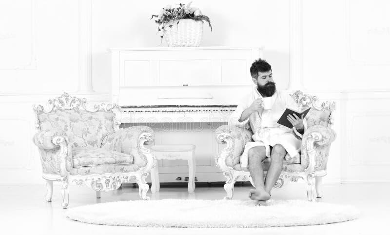 Morgonläsning Intresserad man som läser en bok över en kopp te eller ett kaffe Skäggig grabb isolerat sammanträde i fåtölj in royaltyfria foton
