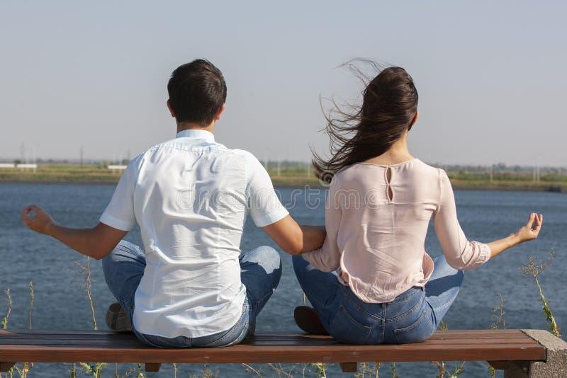 Morgonmeditation Det h?rliga barnet kopplar ihop i vita kl?der som utomhus tillsammans mediterar, och h?lla synar st?ngt arkivbilder