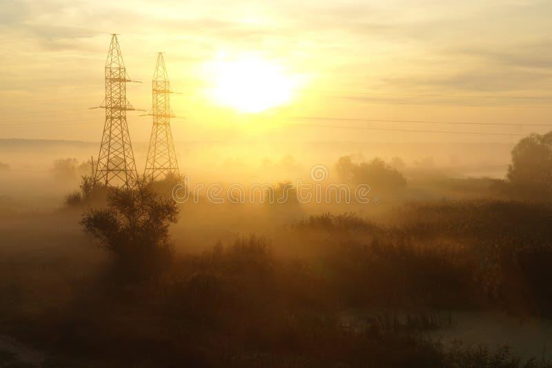 Morgonmist i höstnaturen, orange soluppgångljus i bakgrund royaltyfri fotografi