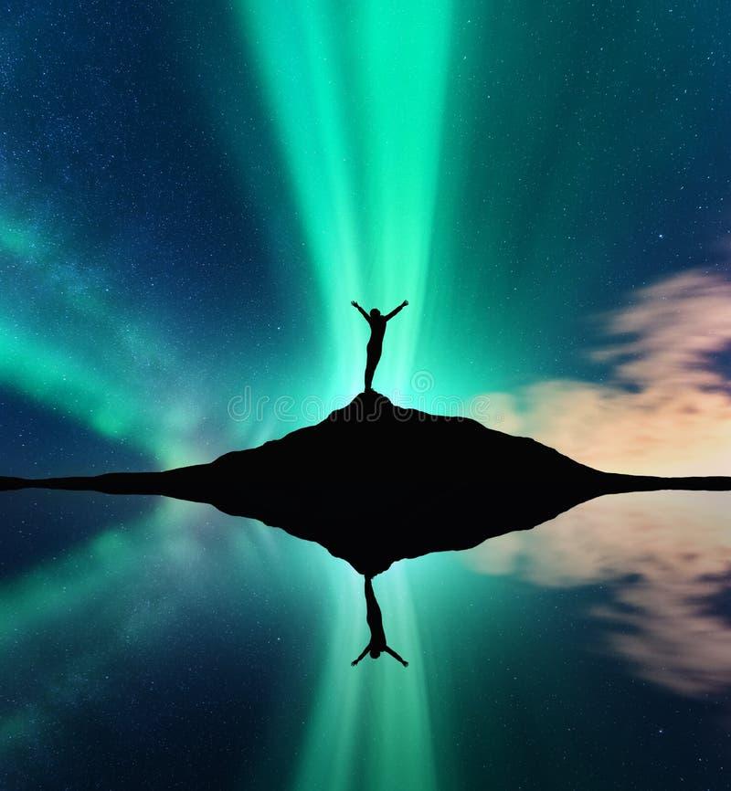 Morgonrodnad, kontur av en kvinna och himmelreflexion i vatten fotografering för bildbyråer