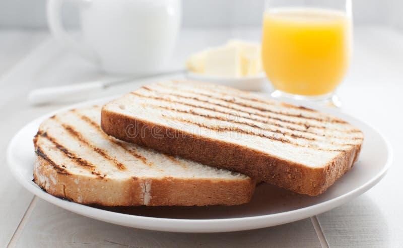 Morgonrostat brödbröd med smör och fruktsaft royaltyfri foto
