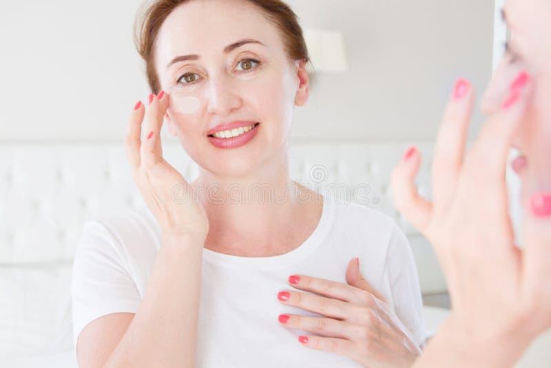 Morgonrutin Kvinnlig som ser i spegel på sovrummet Härlig framsida av den mellersta ålderkvinnan med det kosmetiska fundamentet p royaltyfria foton