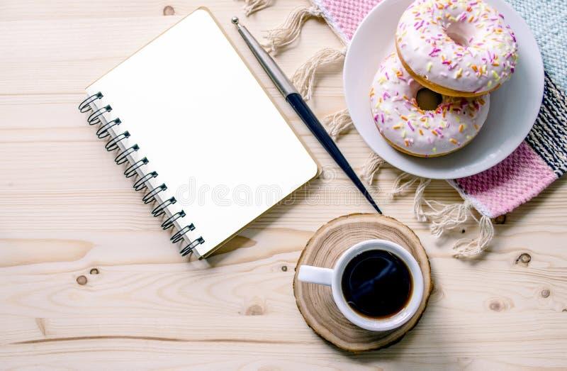 Morgonsammansättning med kaffe och donuts Skrivbord för tabell för kontor för bråklista Inrikesdepartementetarbetsplats royaltyfria bilder