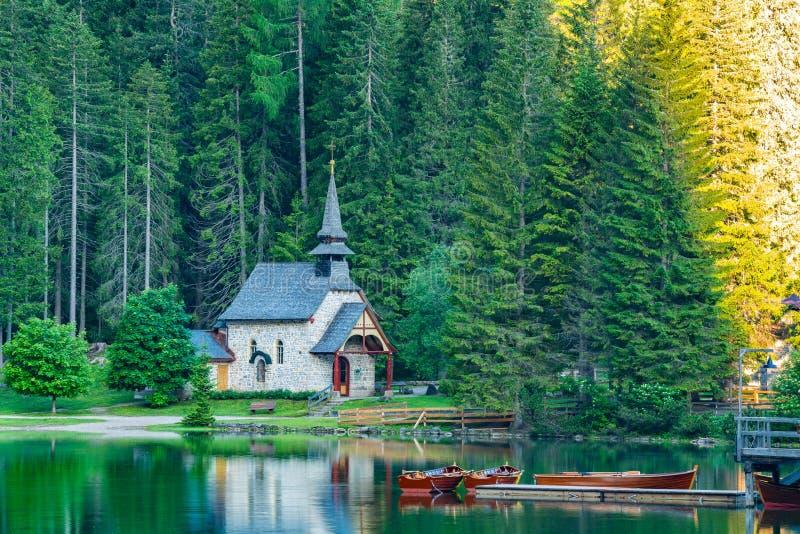 Morgonsikt av den lilla gamla kyrkan på banken av sjön Braies royaltyfri bild