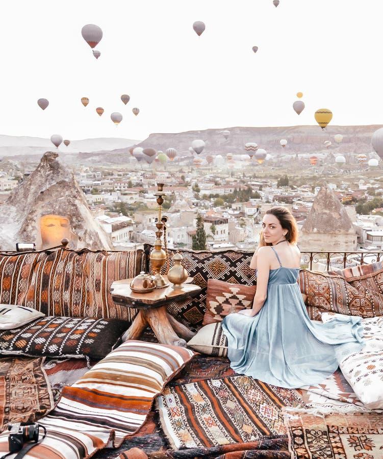 Morgonsikt i Cappadocia Terrassera sikten i den Goreme kvinnan med ballonger och mattor för varm luft arkivbilder