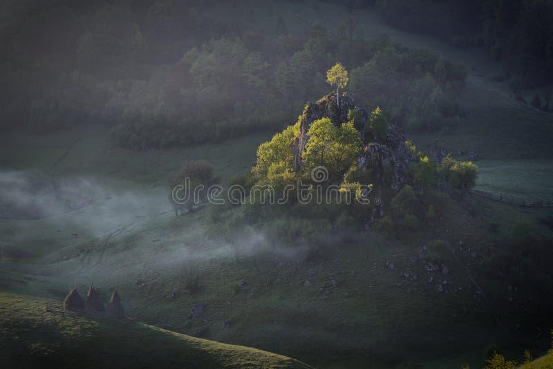 Morgonsolsken med dimma över ett berglandskap med vaggar och träd i direkt solljus Fundatura Ponorului, Rumänien arkivbilder