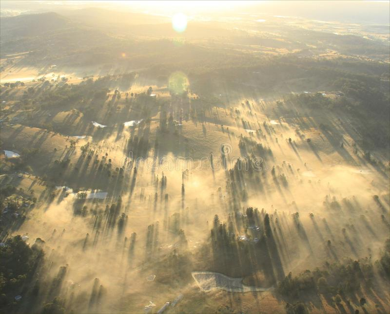 Morgonsoluppgång över stad med lotten av dimma royaltyfria bilder