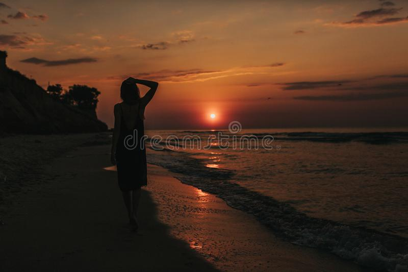 Morgonsoluppgång flickan går på stranden i morgonen Flickakontur på solnedgången kvinnan kopplar av vid havet arkivfoton