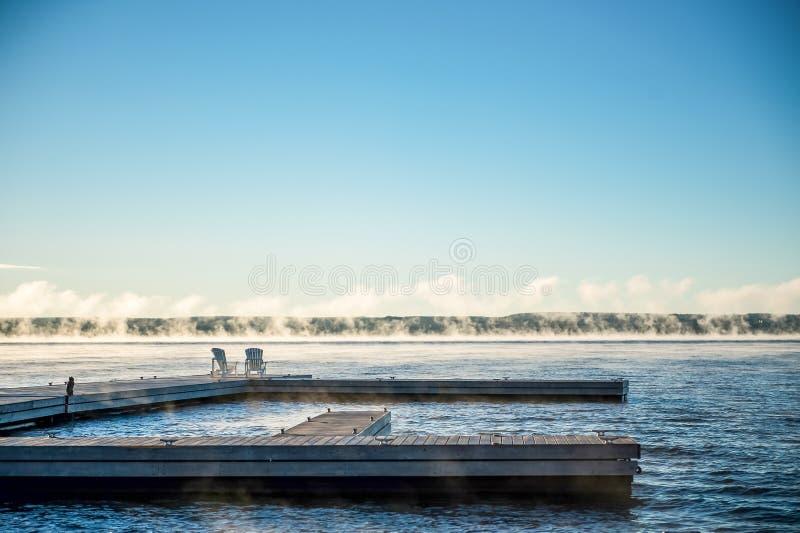 Morgonsoluppgång på en skeppsdocka med Muskoka stolar och mist royaltyfri foto