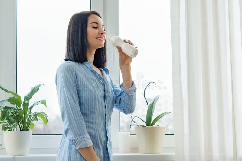 Morgonståenden av ungt le dricka för kvinna mjölkar drinkyoghurt från flaskan, kvinnan som hemma står i skjorta nära fönstret, arkivbild