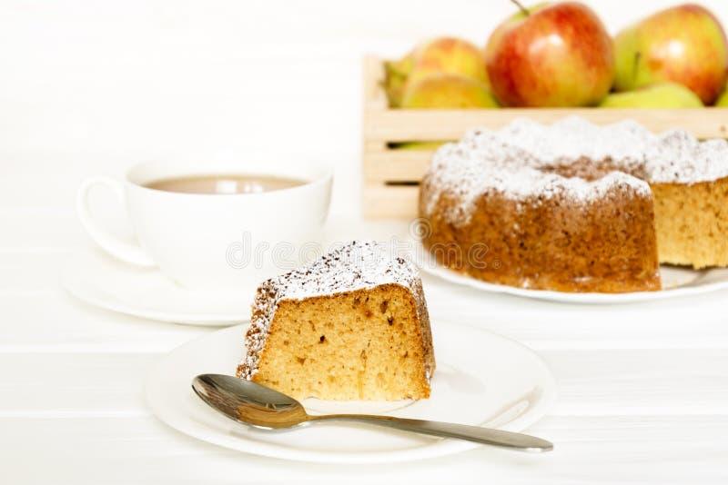 Morgonstilleben med kakan med isläggning tjänade som te och rå äpplen på den vita tabellen Utvalt fokusera fotografering för bildbyråer