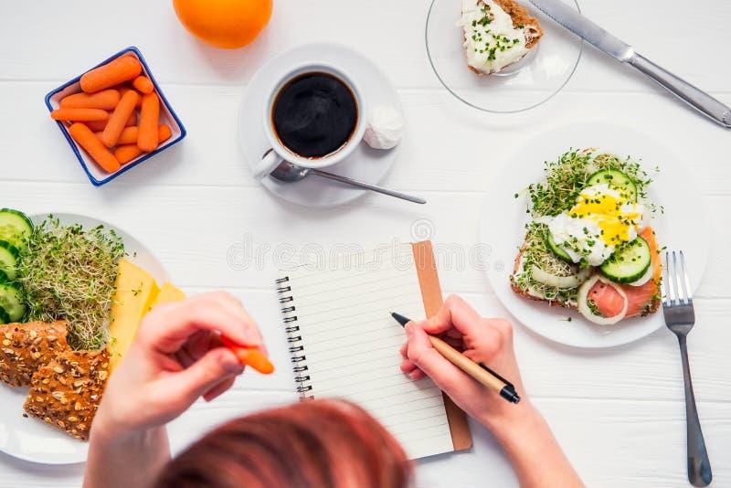 Morgonvanor av lyckat folk Dagplanläggning och sunt mål Kvinna som äter moroten och skriver i den tjänade som anteckningsboken på royaltyfria foton