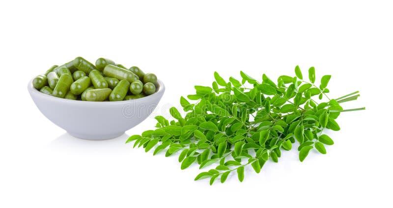Moringa capsules in de kom met blad royalty-vrije stock afbeeldingen