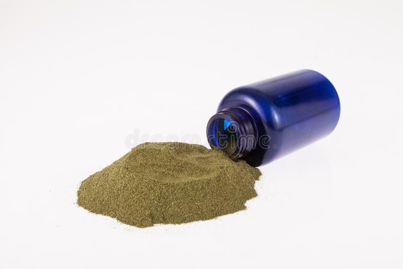 Moringa powder in blue bottle. On neutral background stock photos