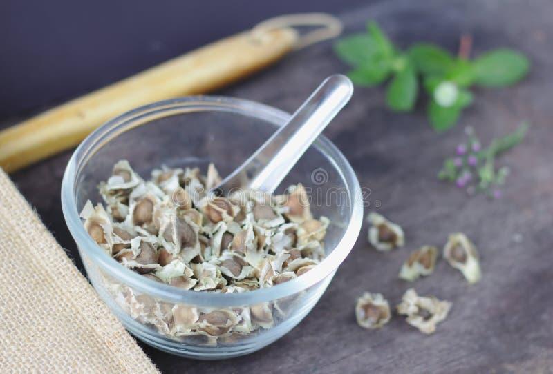 Moringa zaad droog in een duidelijke glaskop, achtergrondlepel, houten blad, bloemzak, gras, houten lepel royalty-vrije stock afbeelding