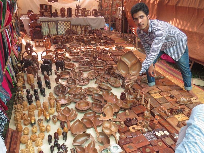 Morjim,印度,2013年11月23日 在买一块木板材的市场、一个印度人展示和提议 库存图片