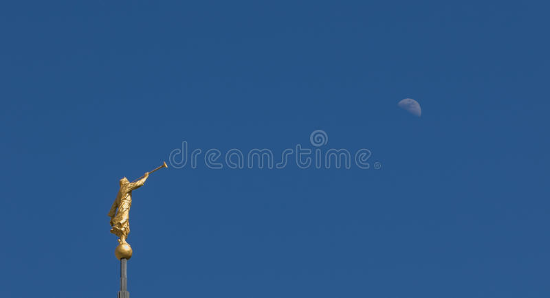 Mormon Angel Moroni Statue. Against a bright blue sky with the Moon royalty free stock image