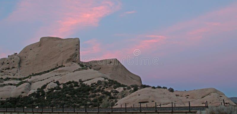 Mormonische Felsen vor Bahnstrecken unter rosa Sonnenuntergang bewölkt sich in hoher Wüste Kaliforniens gerade außerhalb San Bern lizenzfreie stockfotografie