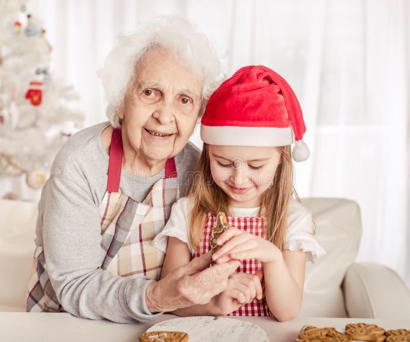 Mormor med dotterdotter som håller bakad kaka arkivbilder