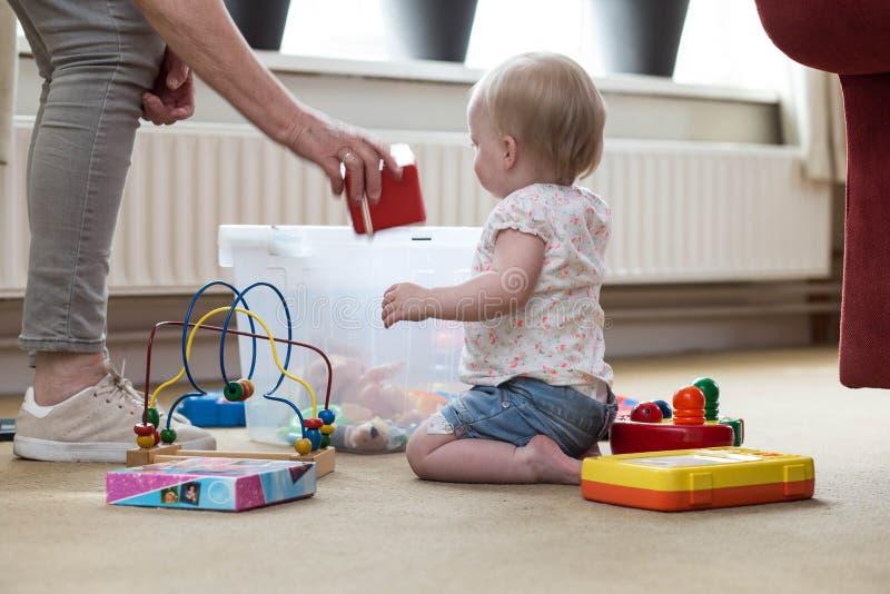 Mormor och att behandla som ett barn med leksaker p? golvet i livingroom fotografering för bildbyråer
