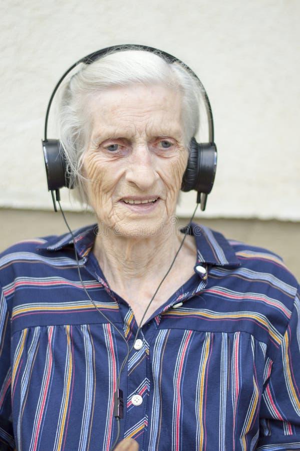 Mormor som lyssnar till musik med hörlurar fotografering för bildbyråer