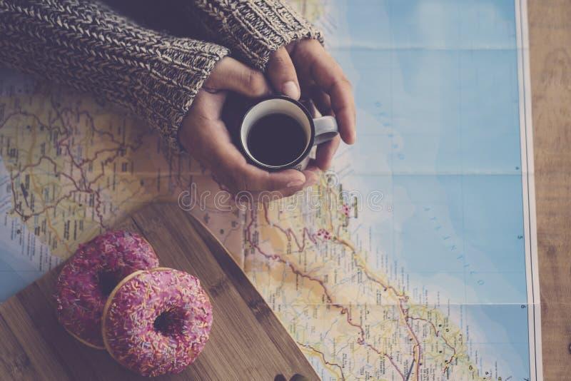 mornig时间上面顶视图与对的采取一个杯子黑意大利咖啡的妇女手看和使用纸地图为下 库存照片